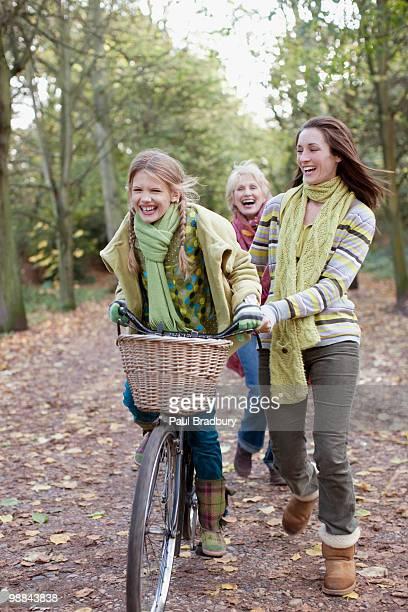 Mutter hilft Tochter mit dem Fahrrad