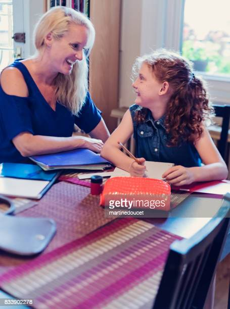 Mother helping daughter to do school homework at home.