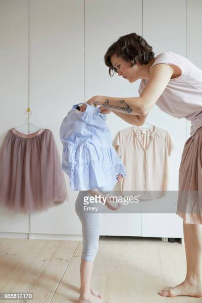 mother helping daughter to dress - routine stock-fotos und bilder