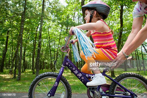 Mother helping daughter to ride bicycle