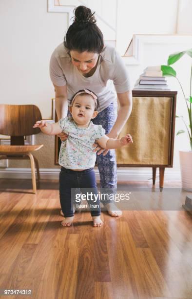 mother helping daughter to walk - primeiros passos - fotografias e filmes do acervo
