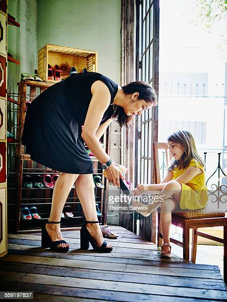 Mother helping daughter try on shoes in shoe store