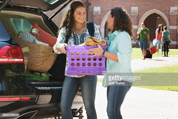 Mother helping daughter unload car at college dormitory