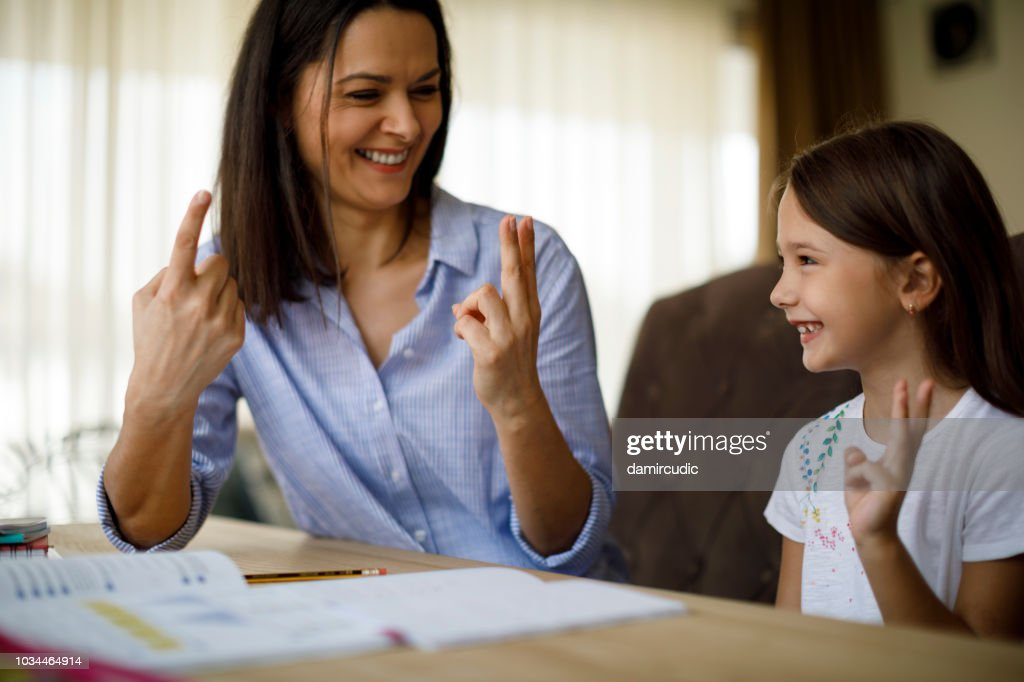 Mother helping daughter with homework : Stock Photo