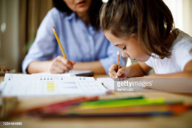 mother helping daughter with homework - sostegno morale foto e immagini stock