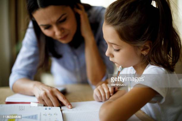 mother helping daughter with homework - home schooling stock pictures, royalty-free photos & images