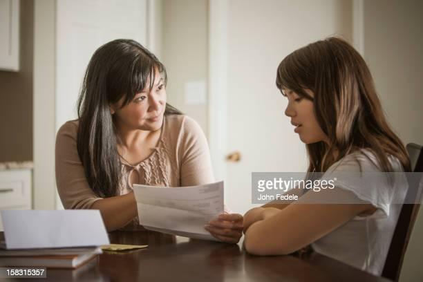 mother helping daughter with homework - boletim escolar imagens e fotografias de stock