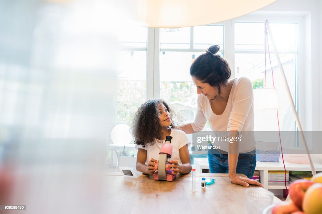 Mother helping daughter with homework, using microscope : Stock Photo