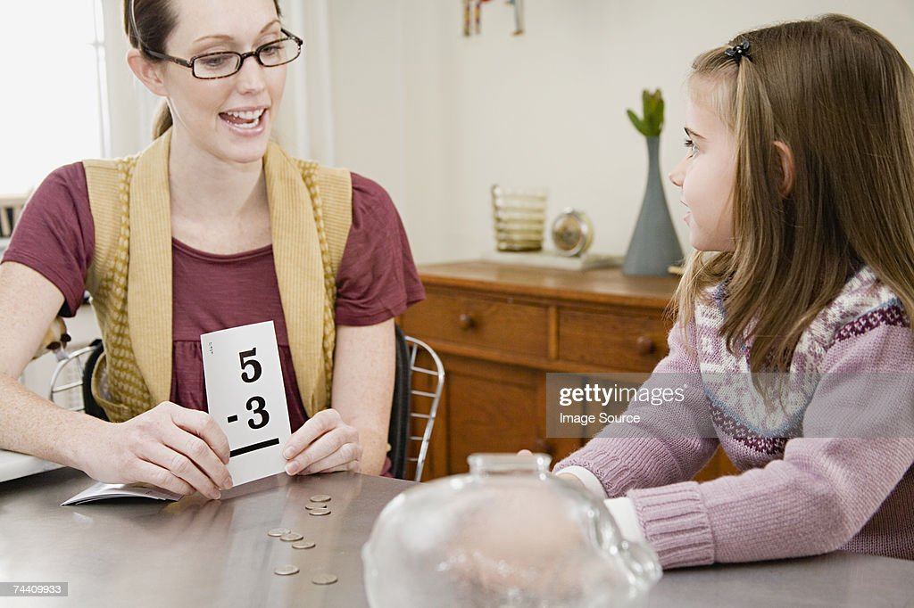 Mother helping daughter with mathematics : Foto de stock