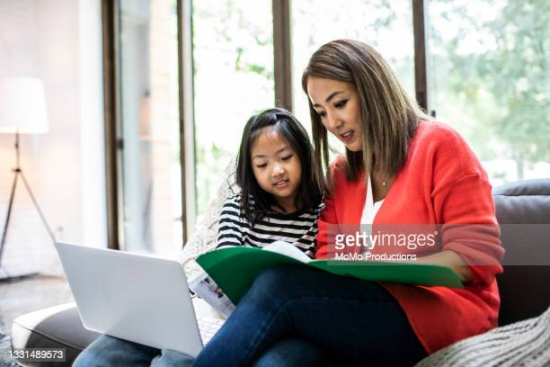mother helping daughter with online e-learning - %e... ストックフォトと画像