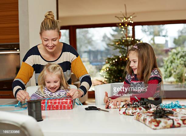 Mother helping daughters with wrapping up presents