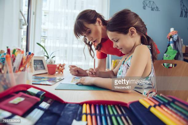 mother helping girl doing her schoolwork at home - pencil case stock photos and pictures