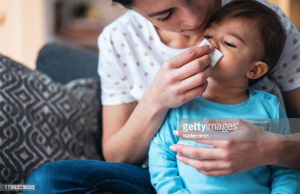 mother helping her baby son to blow his nose - blowing nose stock pictures, royalty-free photos & images