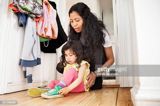 mother helping her daughter getting dressed