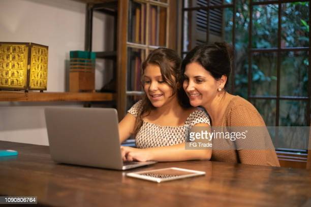 mother helping her daughter in the homework at home - one parent stock pictures, royalty-free photos & images