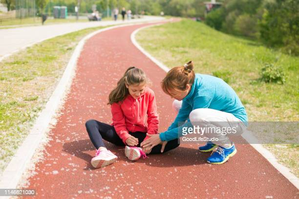 mother helping her daughter - ankle stock pictures, royalty-free photos & images