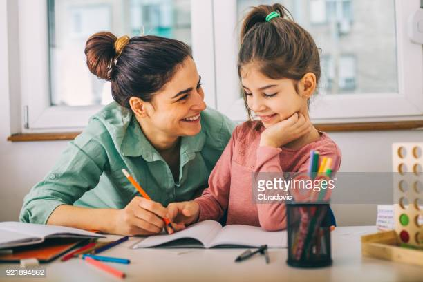 Mother Helping Her Daughter While Studying