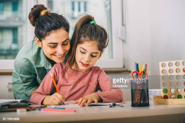 mother helping her daughter while studying - a helping hand stock pictures, royalty-free photos & images