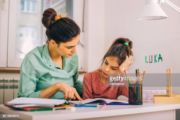 Madre ayudando a su hija cuando estudian