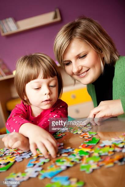 Mãe ajudando a filha com o'puzzle'