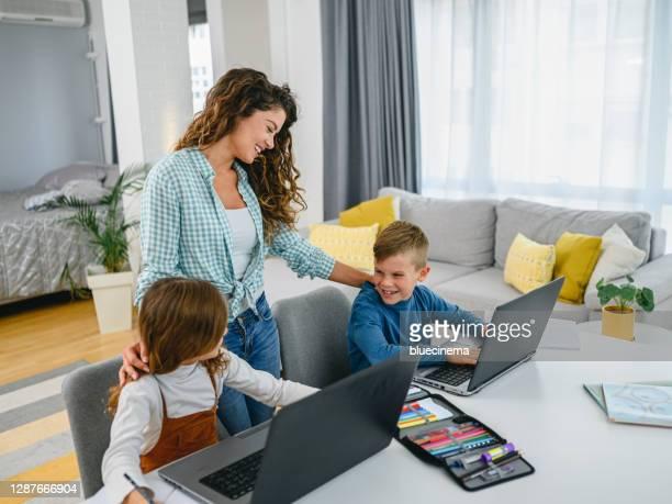 母親説明她的孩子進行在線教育 - 跟拍鏡頭 個照片及圖片檔
