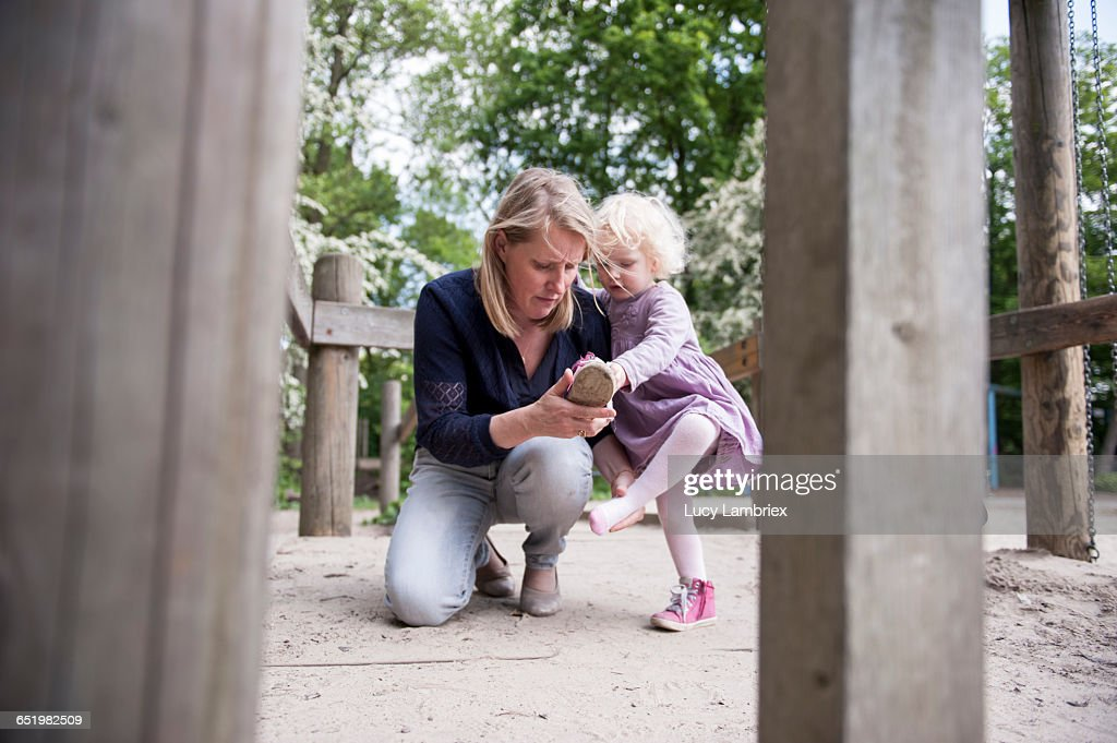 Mother helping her little daughter with her shoe : Stockfoto