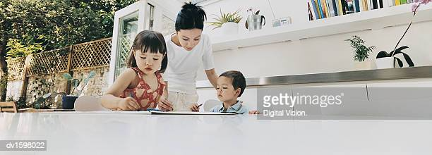 Mother Helping Her Son and Daughter to Colour In at the Dining Room Table