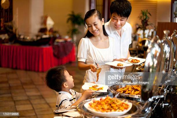 Mother helping her son at a buffet