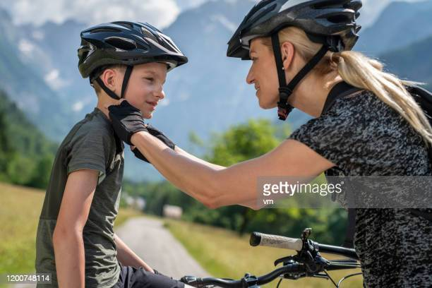 mother helping her son fasten his cycling helmet - cycling helmet stock pictures, royalty-free photos & images