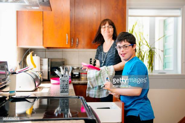 Mother helping her son of 12 years old with Autism and Down Syndrome in daily lives emptying the dishwasher