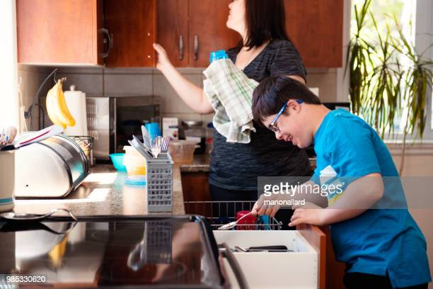mother helping her son of 12 years old with autism and down syndrome in daily lives emptying the dishwasher - autismo foto e immagini stock
