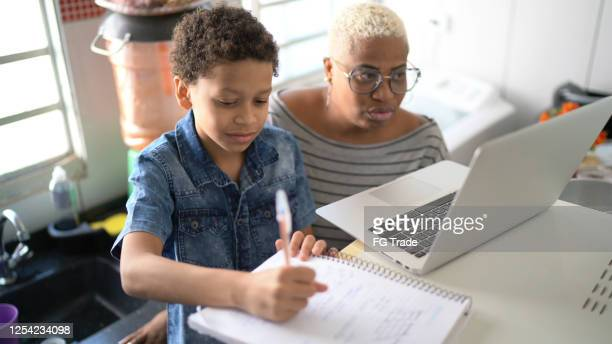 mother helping her son studying with laptop on a online class at home - remote location stock pictures, royalty-free photos & images