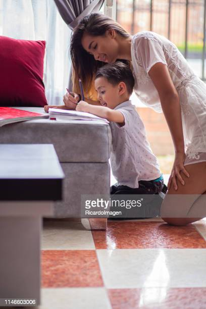 Mother helping her son to do homework inside