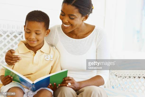Mother helping her son to reading a book