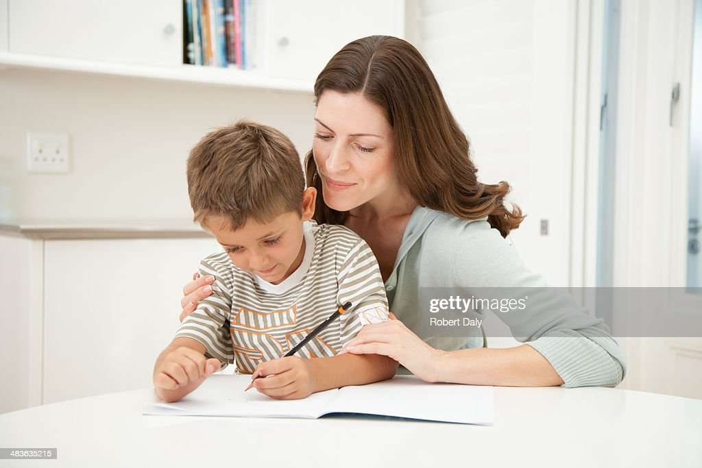 A mother helping her son with his homework : Stock Photo