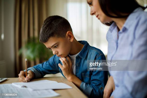 mother helping her son with homework - struggle stock pictures, royalty-free photos & images