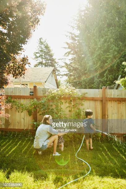 Mother helping infant daughter stand in backyard while son waters plants on summer morning