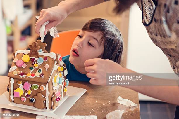 Mother helping little boy to decorate gingerbread house.