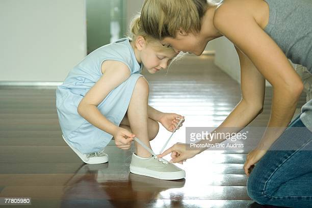 mother helping little girl tie shoe laces - shoelace stock pictures, royalty-free photos & images