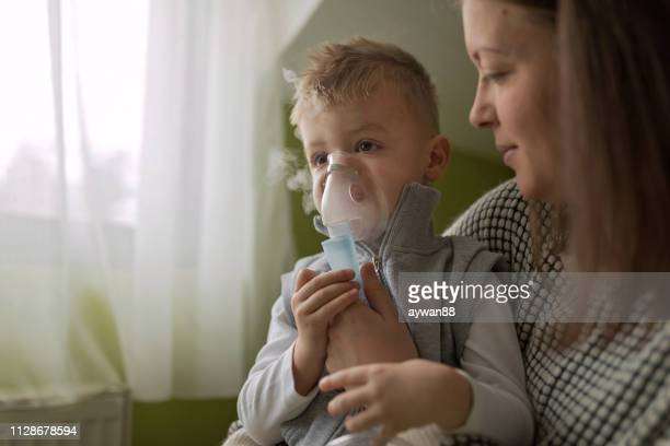 mother helping little son using nebulizer during inhalation - asthma stock pictures, royalty-free photos & images