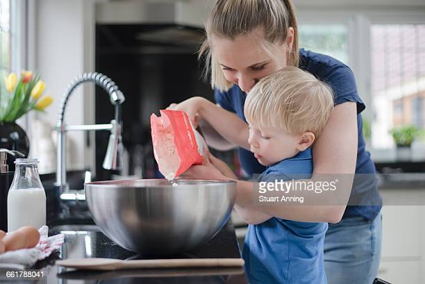 Mother helping son bake cake