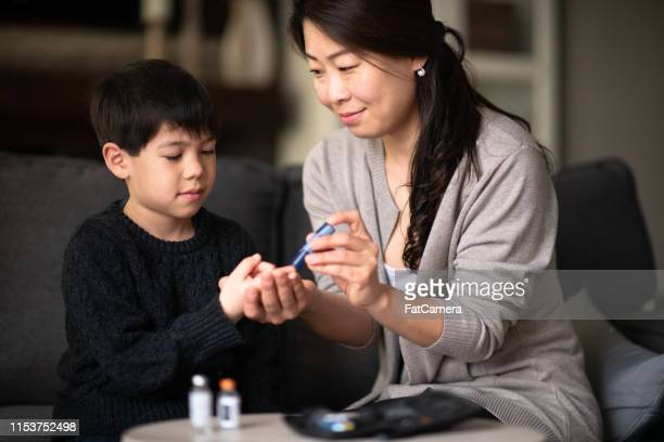 mother helping son check blood sugar levels - insulin stock pictures, royalty-free photos & images