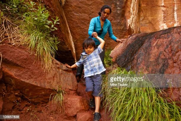 mother helping son climb down rocks - 岩壁 ストックフォトと画像