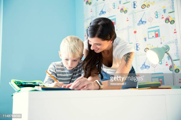 mother helping son doing homework at desk - home schooling stock pictures, royalty-free photos & images