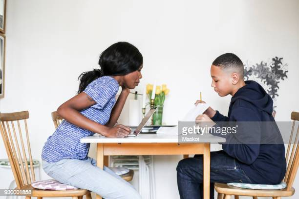 Mother helping son doing homework at dining table in house