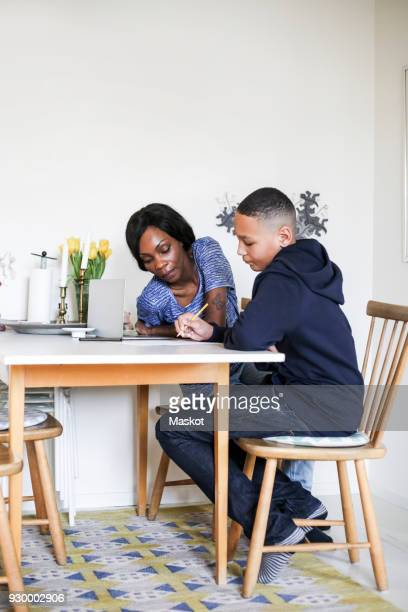 Mother helping son doing homework at dining table