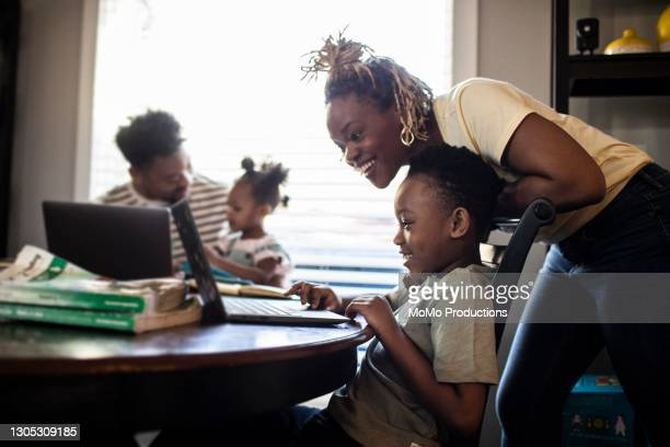 mother helping son during e-learning at home - education stock pictures, royalty-free photos & images