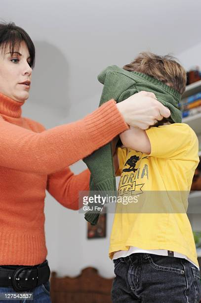 Mother helping son get dressed