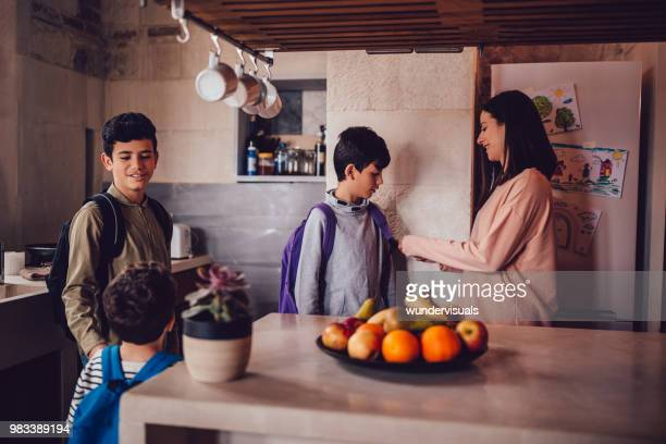 mother helping son get ready before leaving for school - sayings stock pictures, royalty-free photos & images