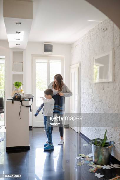 mother helping son put on sweater for school - coat stock pictures, royalty-free photos & images